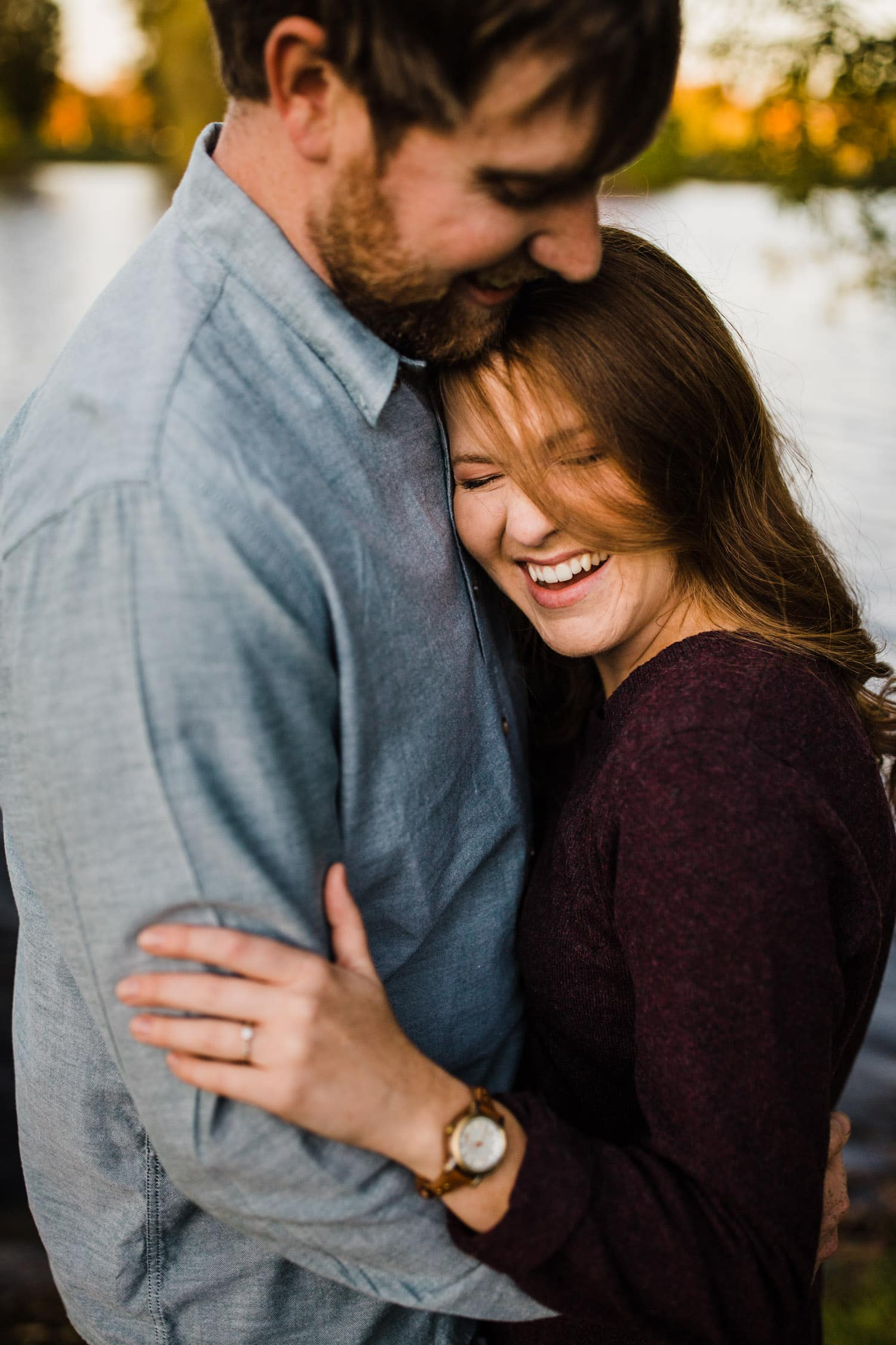 couple cuddle and laugh together outside - ottawa engagement photographer