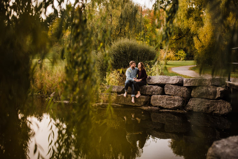 couple sit along rocks by pond - ottawa arboretum engagement