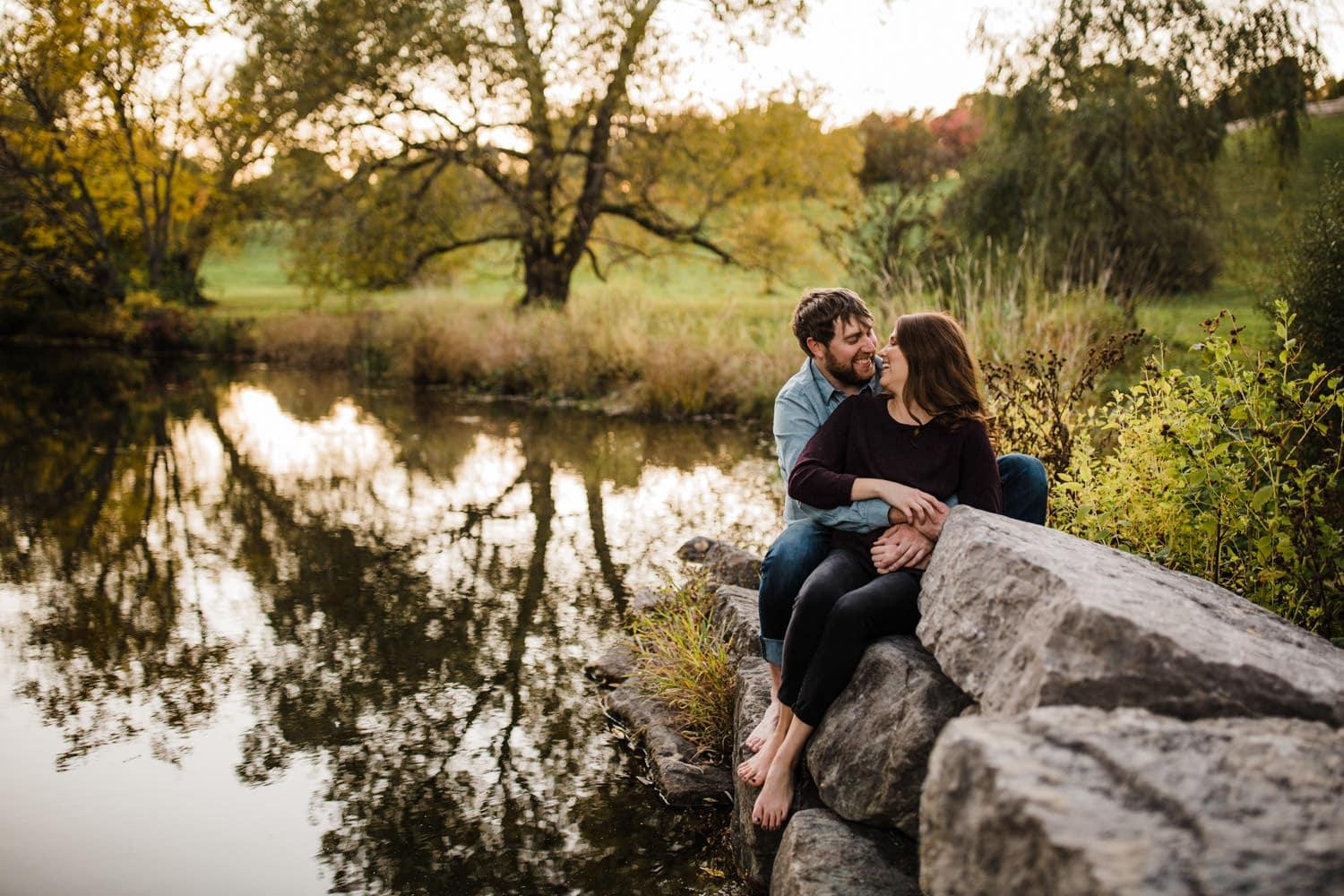 couple sit on rocks together by pond - ottawa fall engagement