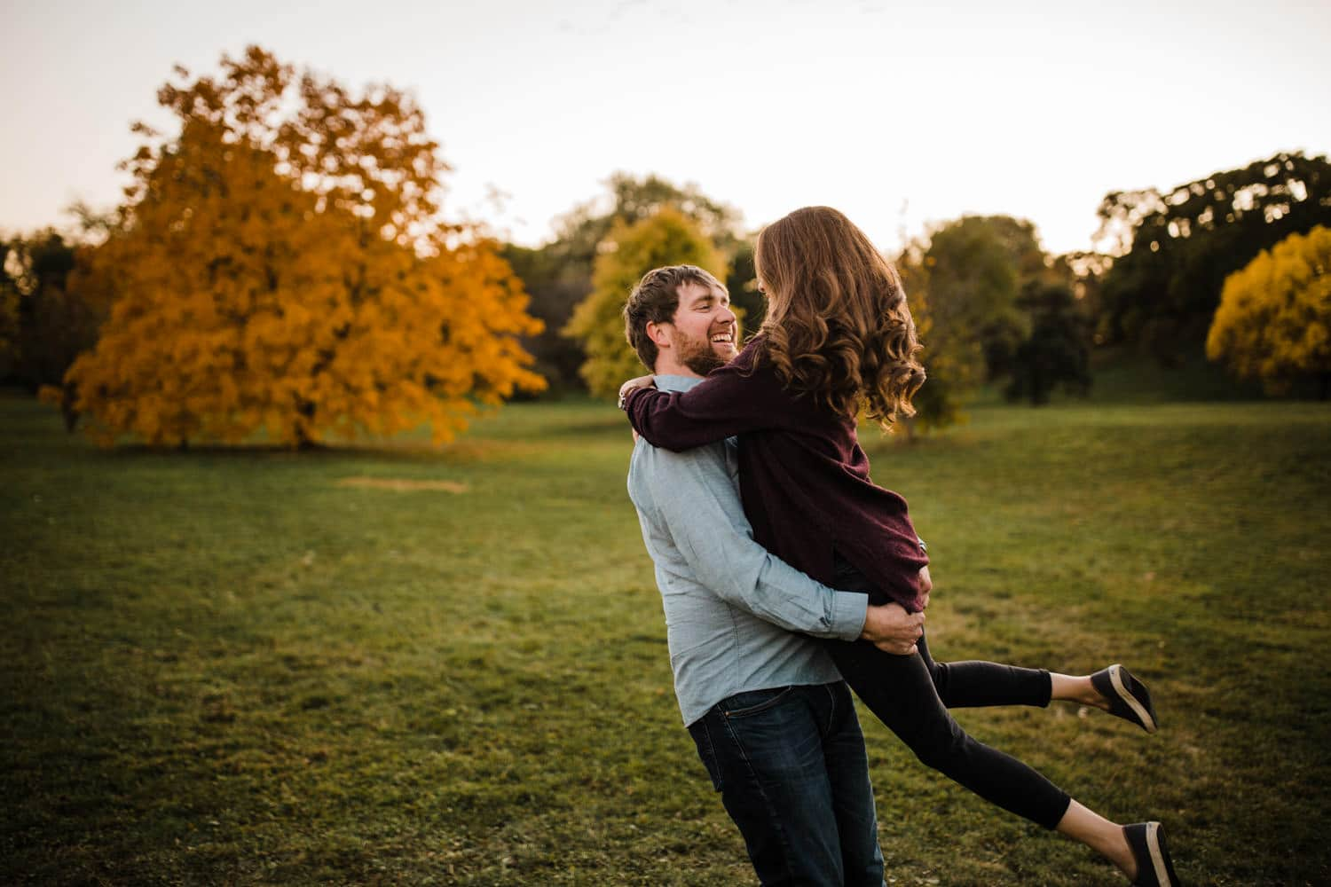 couple spin together outside in a park - ottawa fall engagement