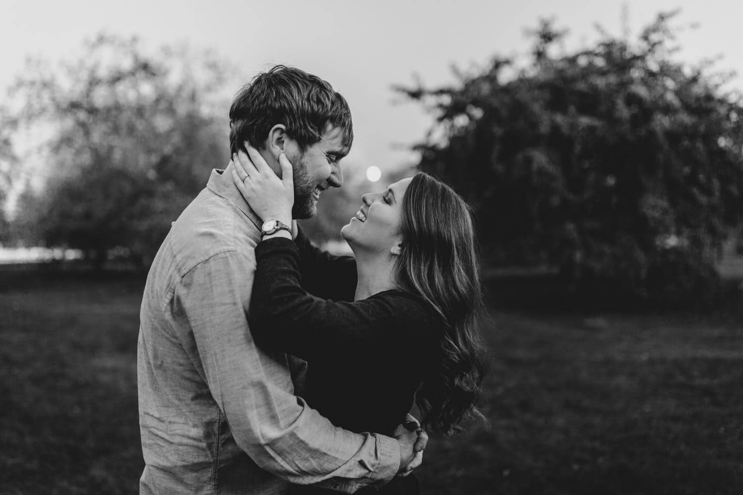 woman holds mans face and laughs - ottawa fall engagement