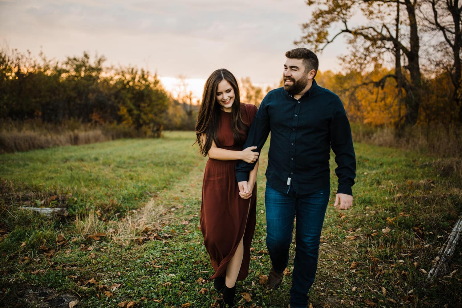 couple walk hand in hand together outside