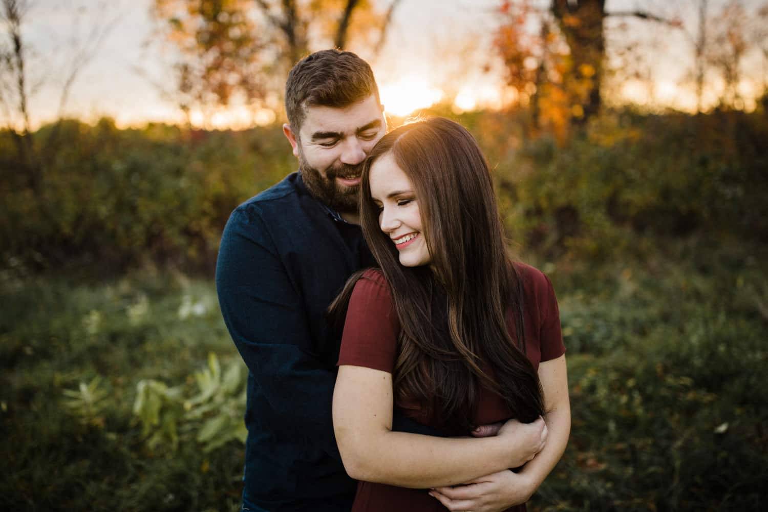 couple stand in a field together at sunset - ottawa fall engagement