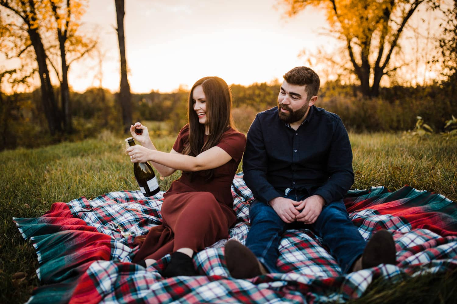 engaged couple pop champagne during outdoor fall engagement session
