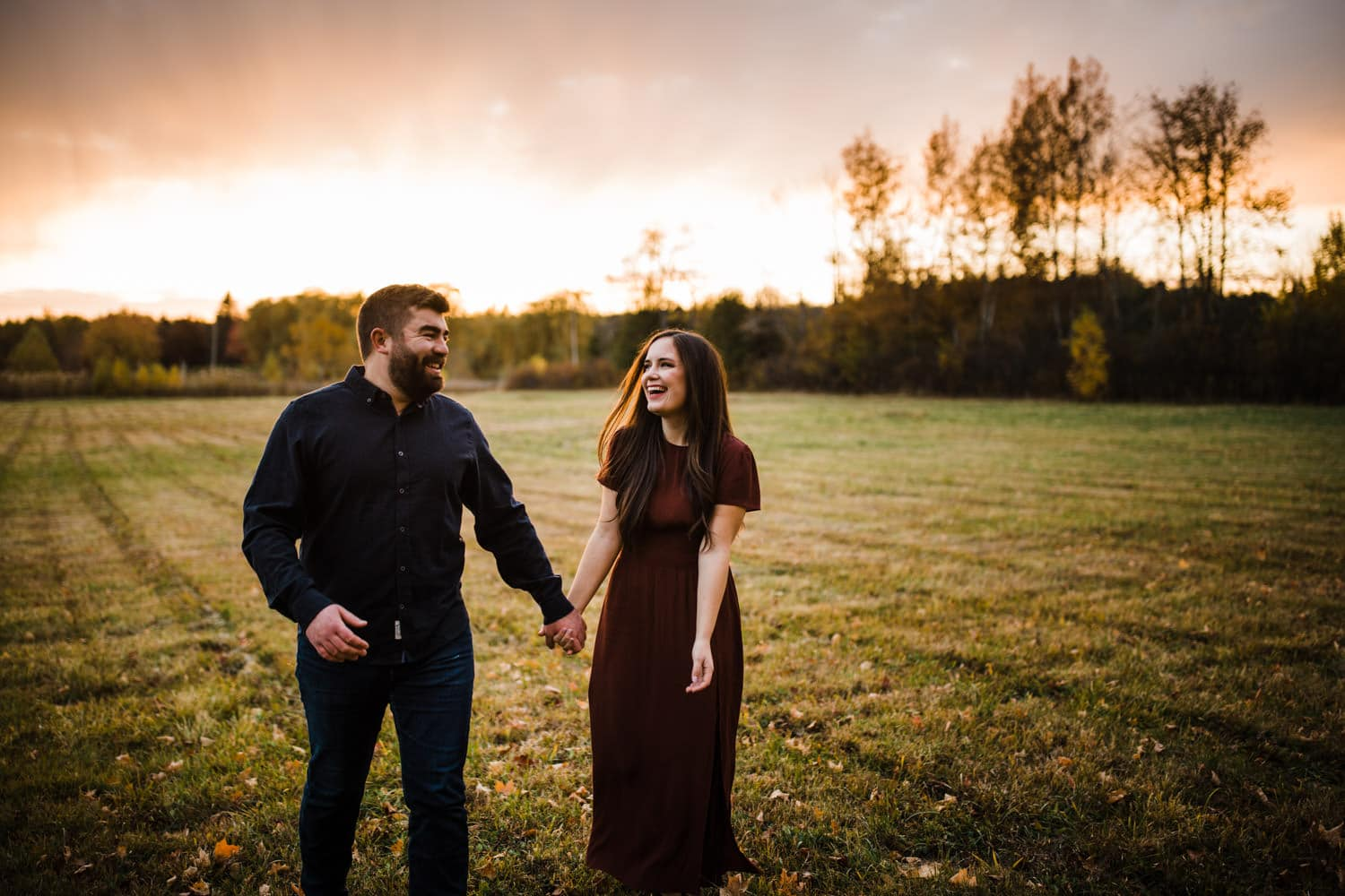 couple walk through an open field together