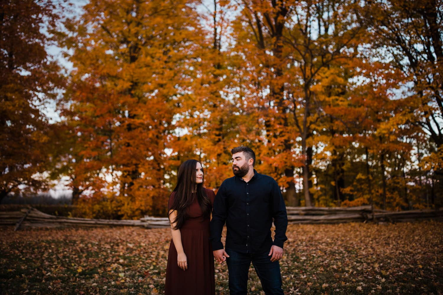 couple hold hands and look at one another - ottawa fall engagement