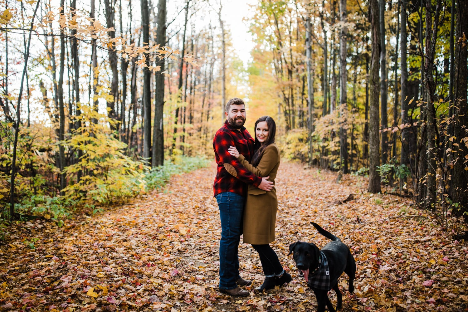 couple stands close on a trail together while dog runs around them