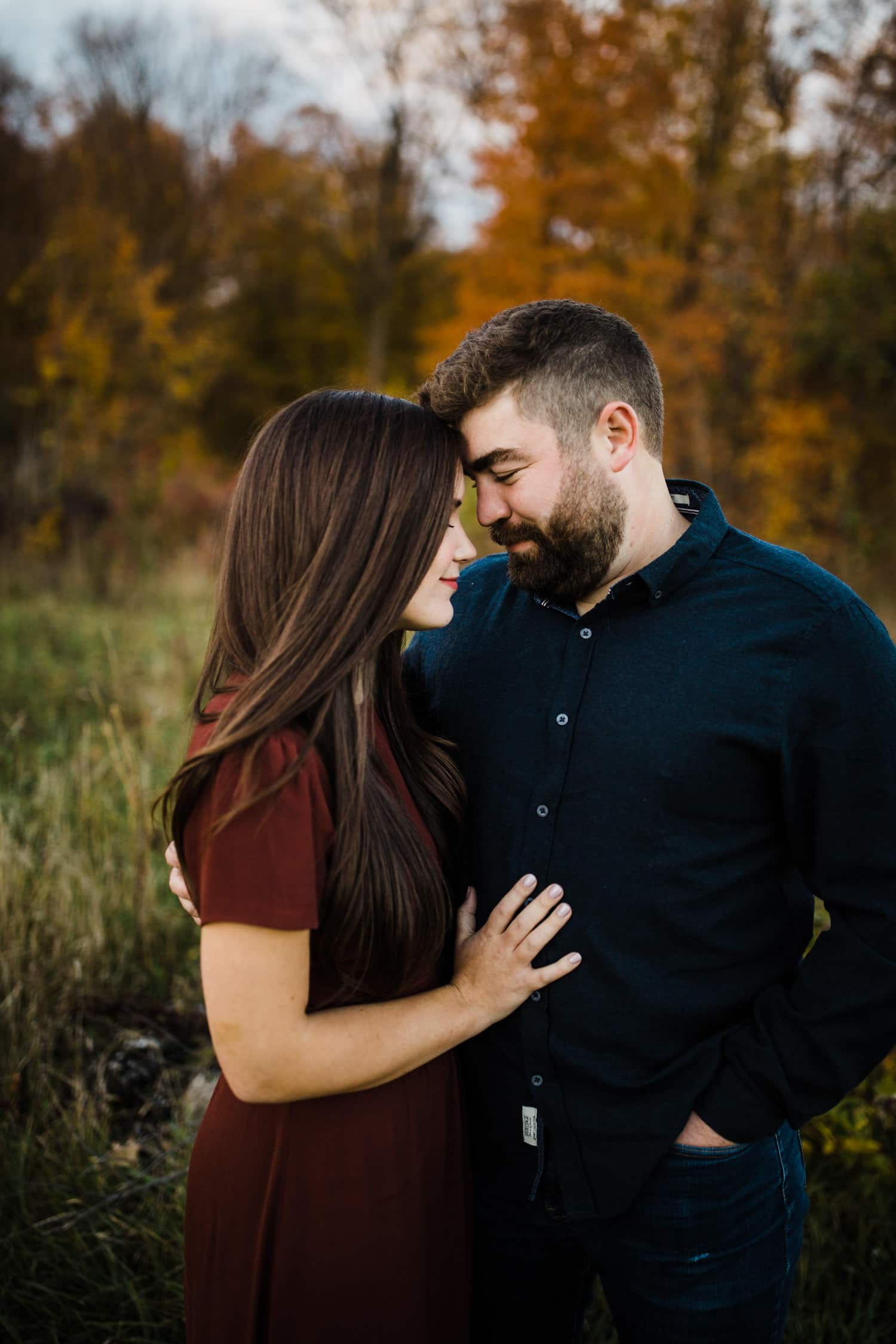 couple stand together for fall engagement session