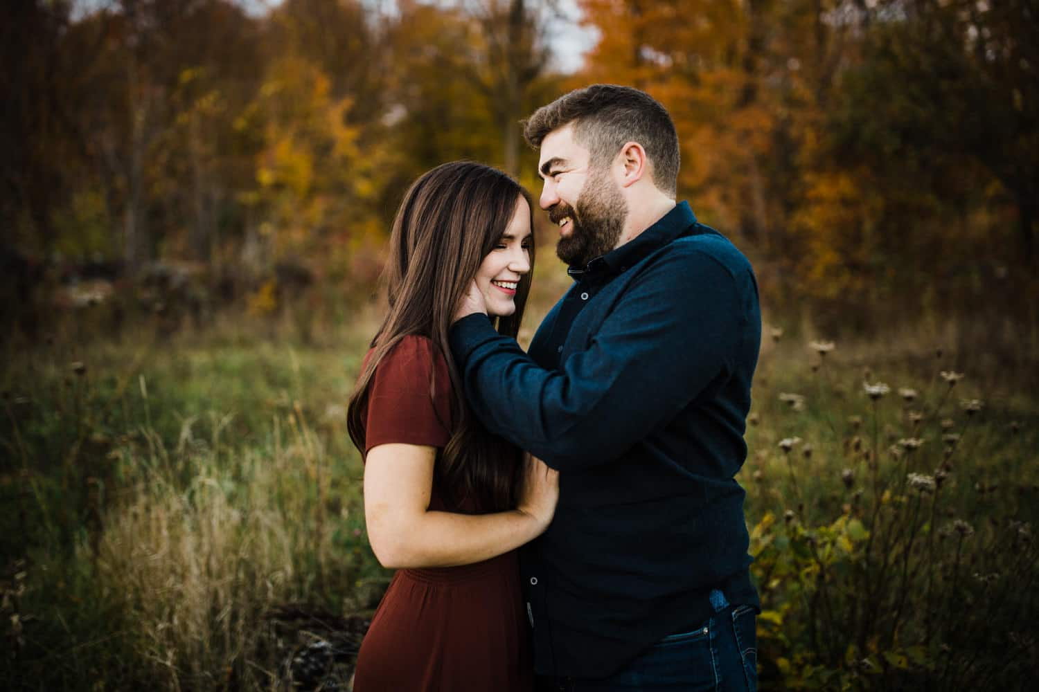 couple laugh in a field together - ottawa fall engagement