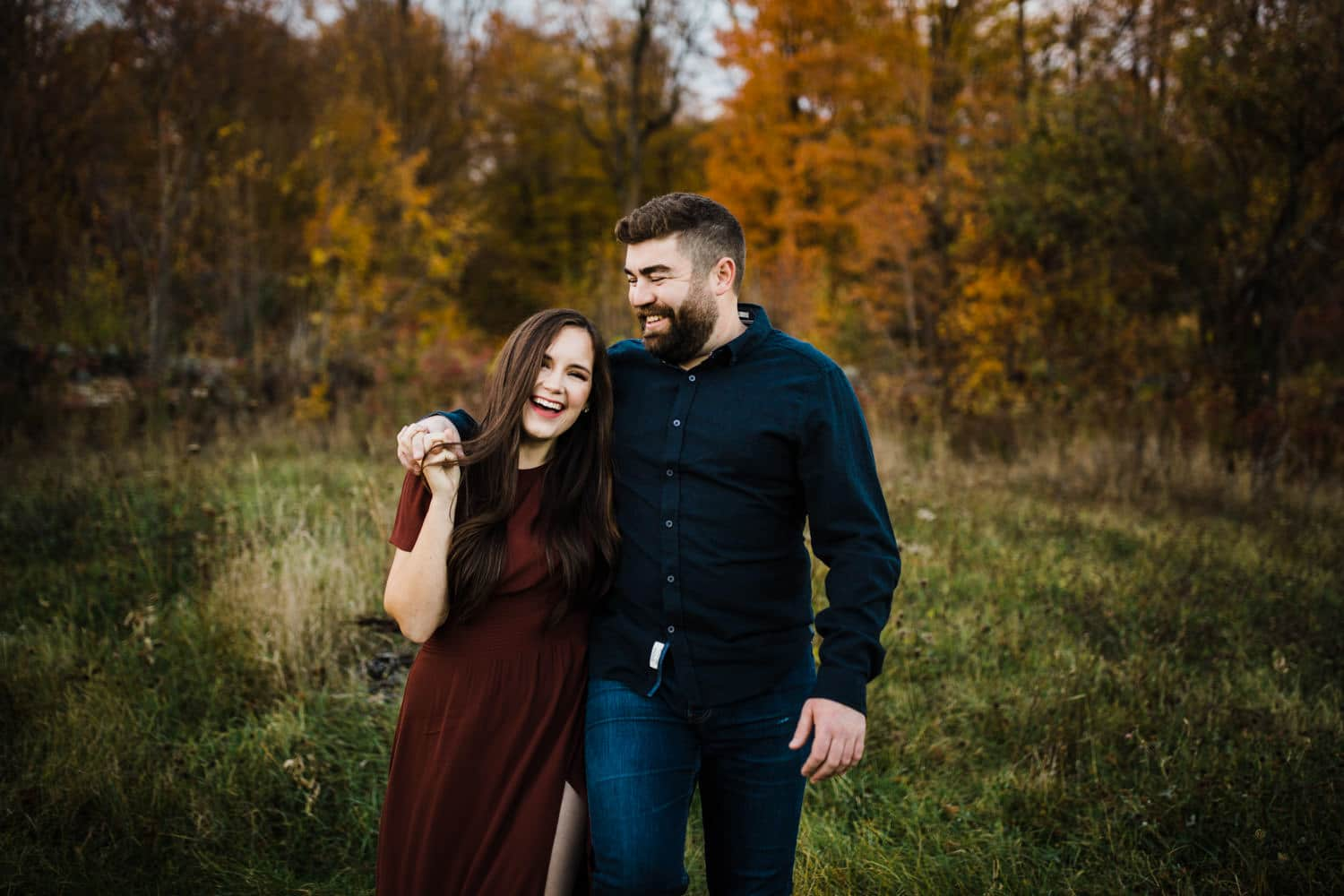 couple hold hands and laugh together outside - ottawa fall engagement
