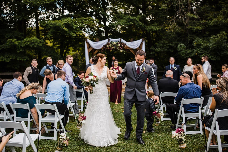 couple walk down the aisle with their son - ottawa outdoor wedding