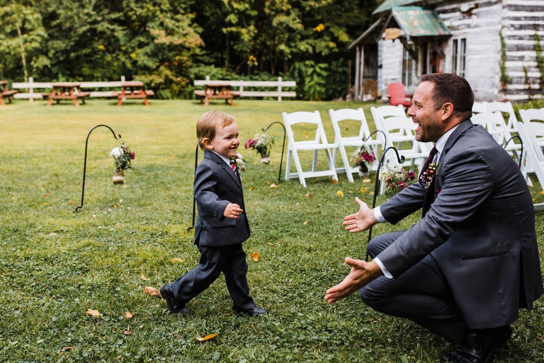 ring bearer runs toward his dad - outdoor fall wedding