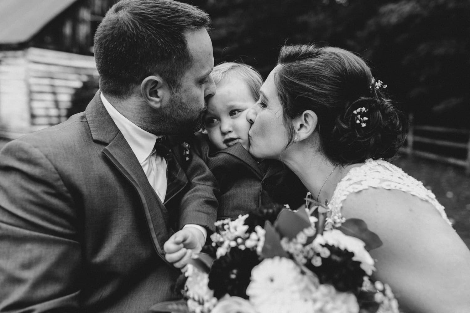 bride and groom kiss their young son - outdoor fall wedding