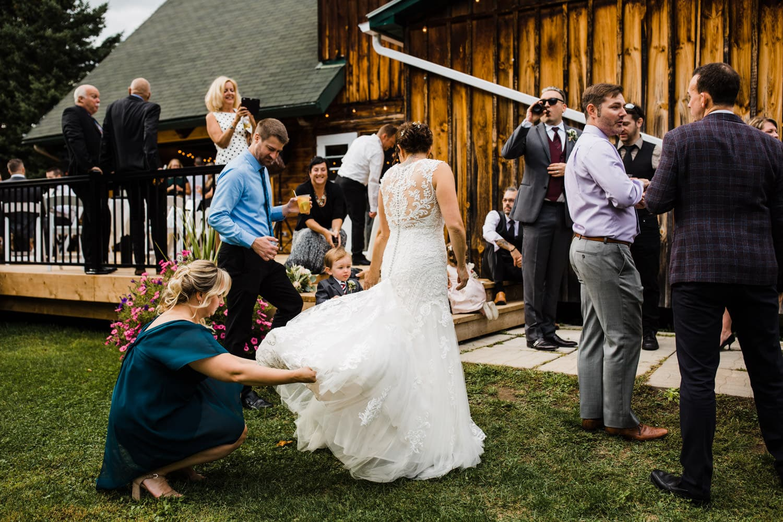 a friend bustles the bride's dress - station 4 saisons wedding