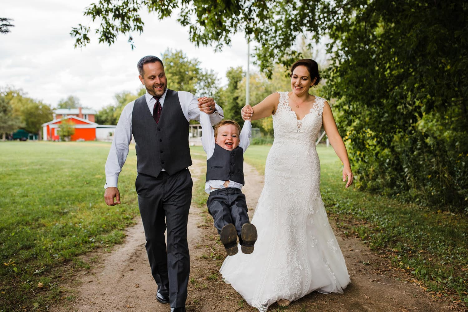 bride and groom swing their young son - station 4 saisons wedding