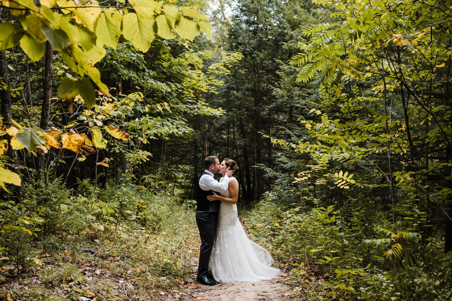 bride and groom kiss in forest - station 4 saisons wedding