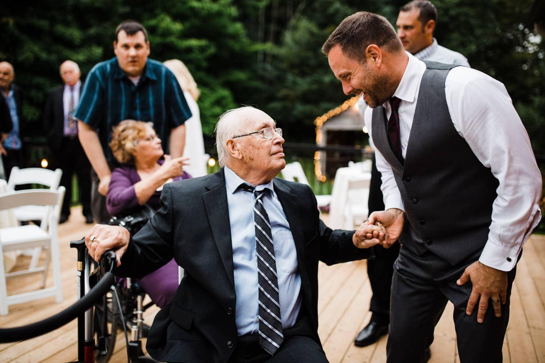 groom talks with grandfather at wedding reception - outdoor ottawa wedding