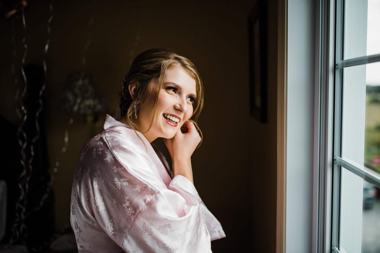 bride puts on her earrings and looks out window - strathmere summer wedding