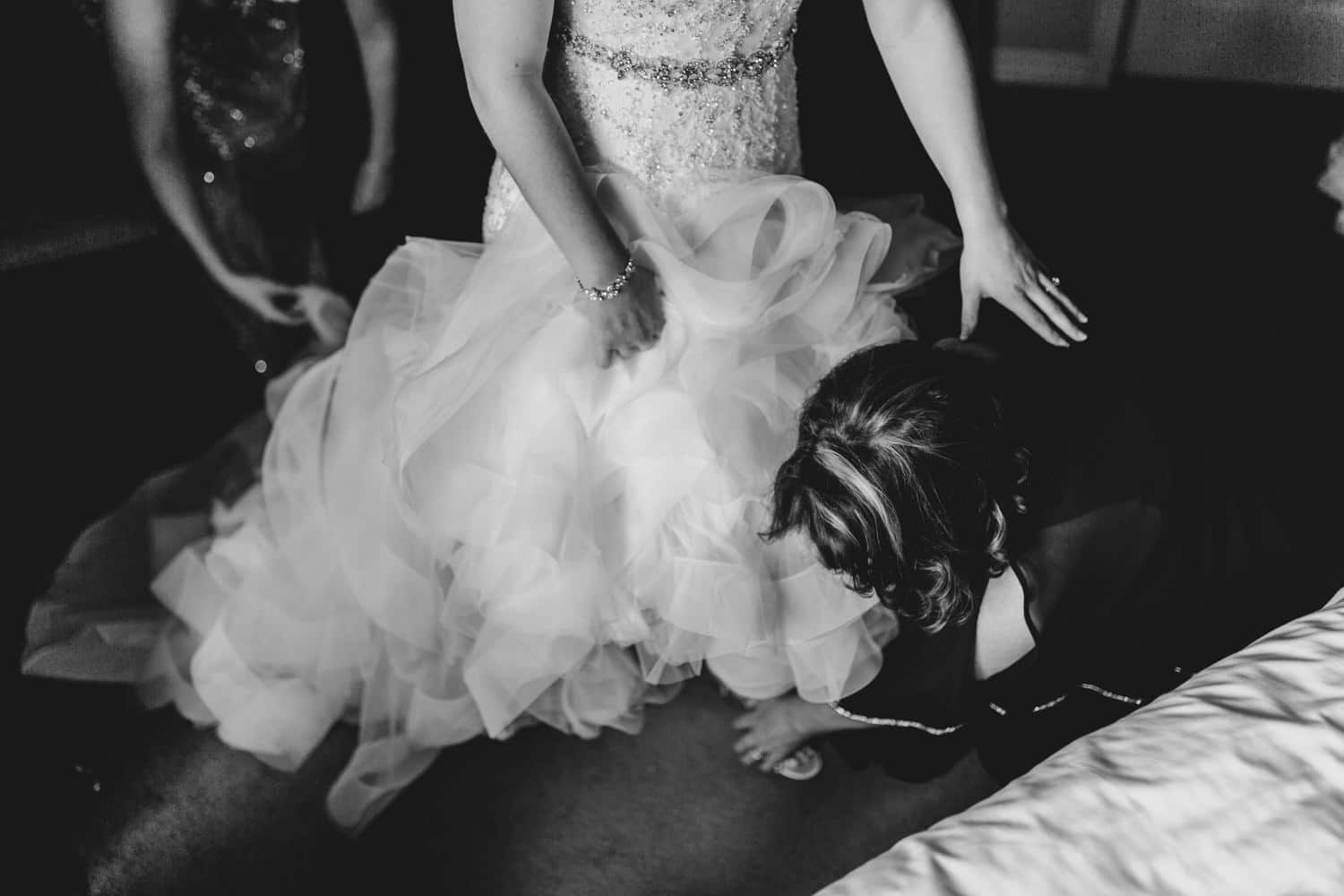 bride's mom helps her put her shoes on
