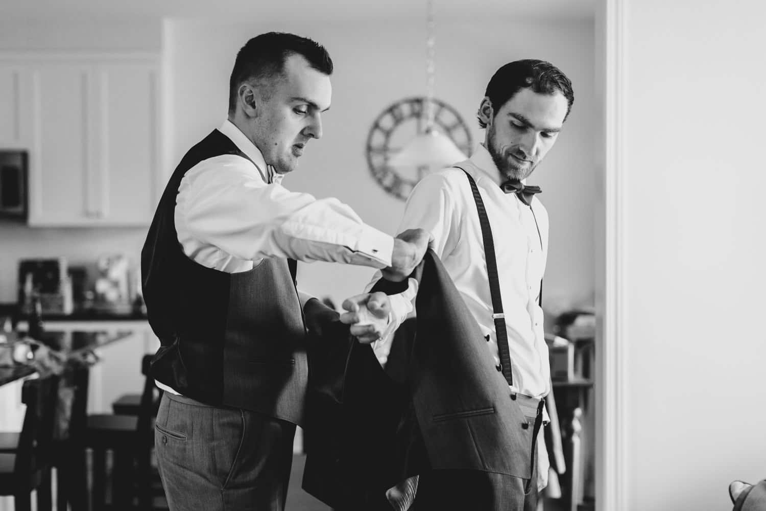 groom's brother helps him put his vest on
