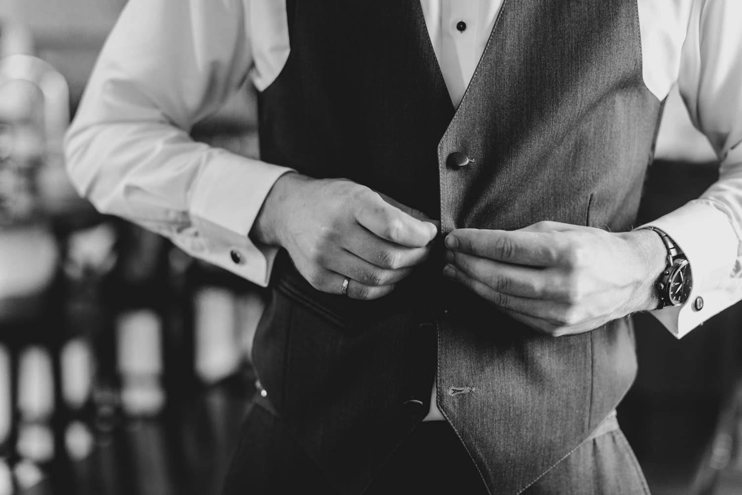 groom does up buttons on his vest