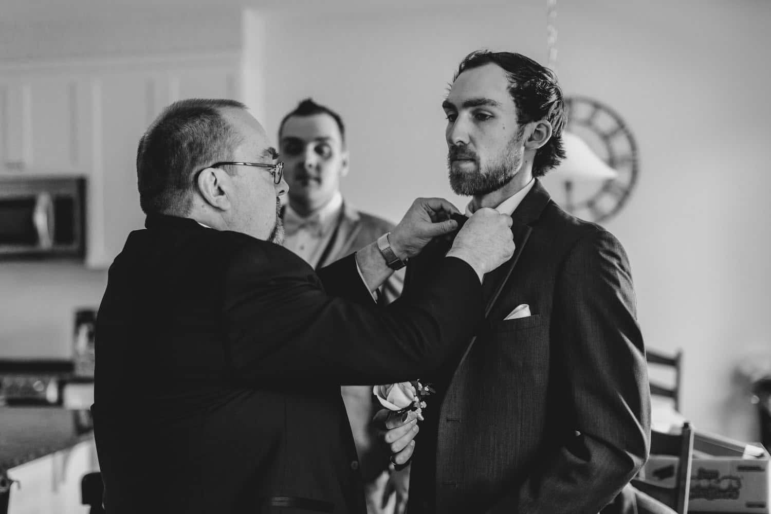 groom's father helps him with bow tie