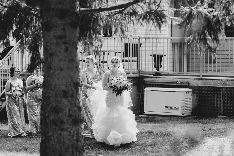 bride walks toward garden with bridesmaid carrying her dress behind her