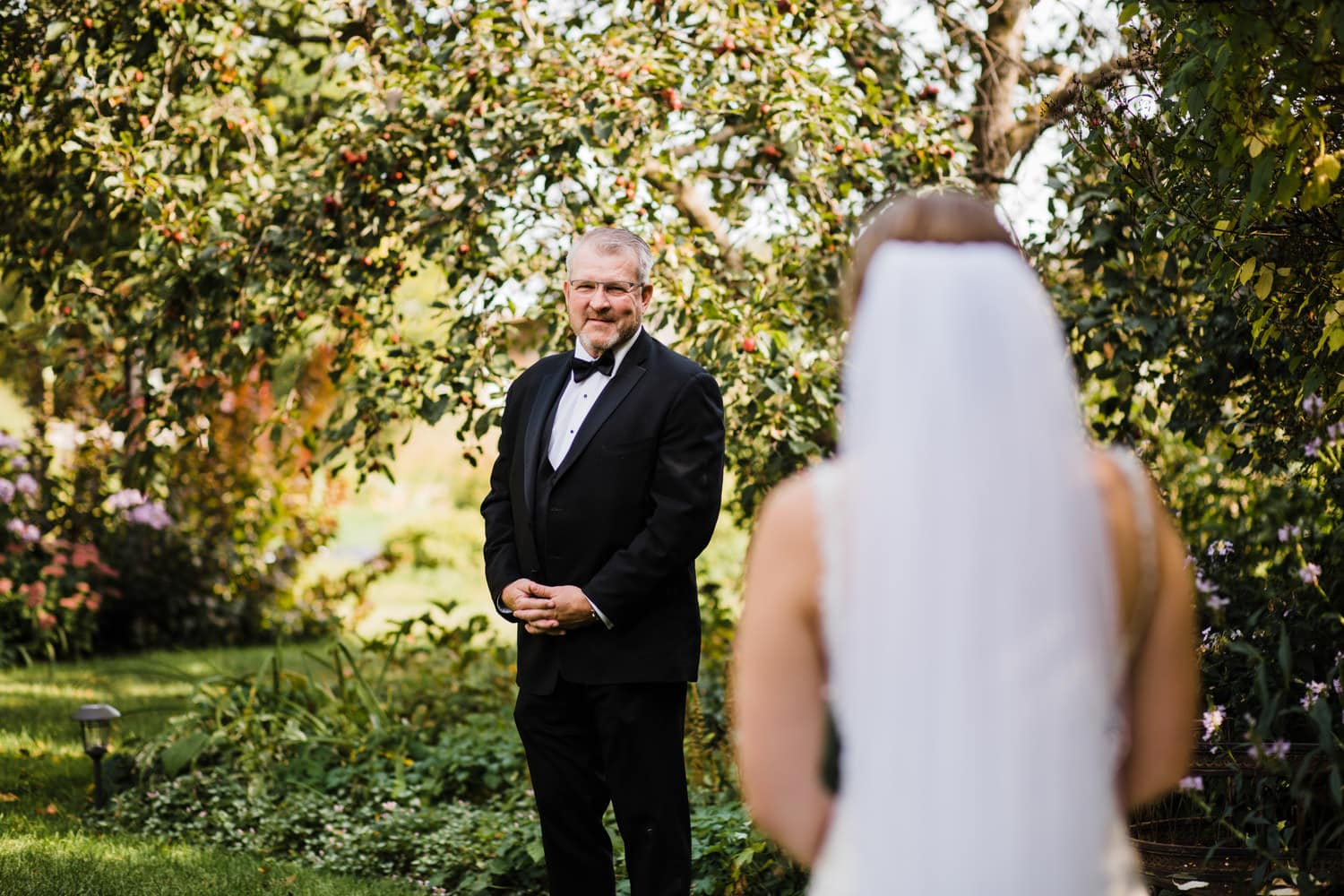 bride's first look with her father inside garden