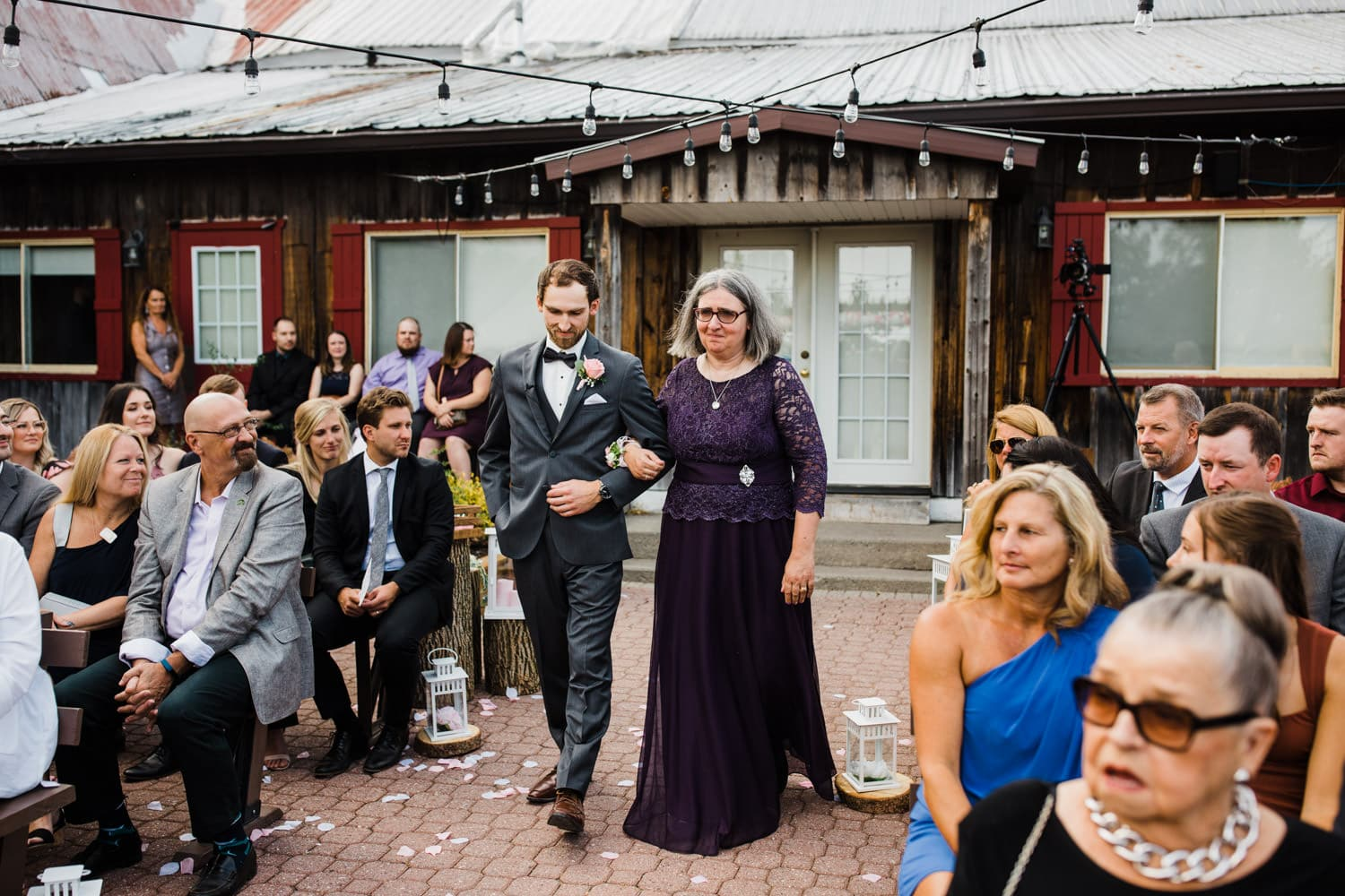 groom walks down aisle with his mother