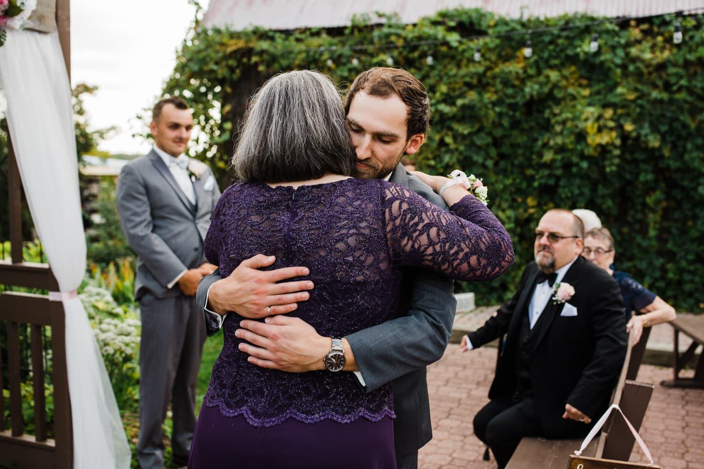 groom hugs his mom at wedding ceremony - strathmere summer wedding