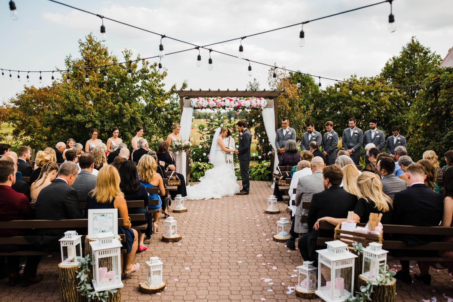 bride and groom bow their heads during wedding ceremony - strathmere summer wedding