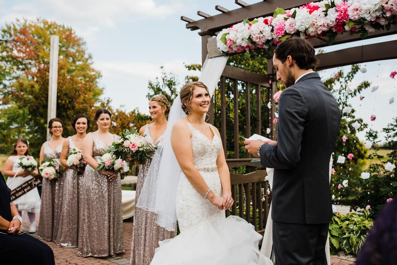 bride laughs during vows - outdoor summer wedding