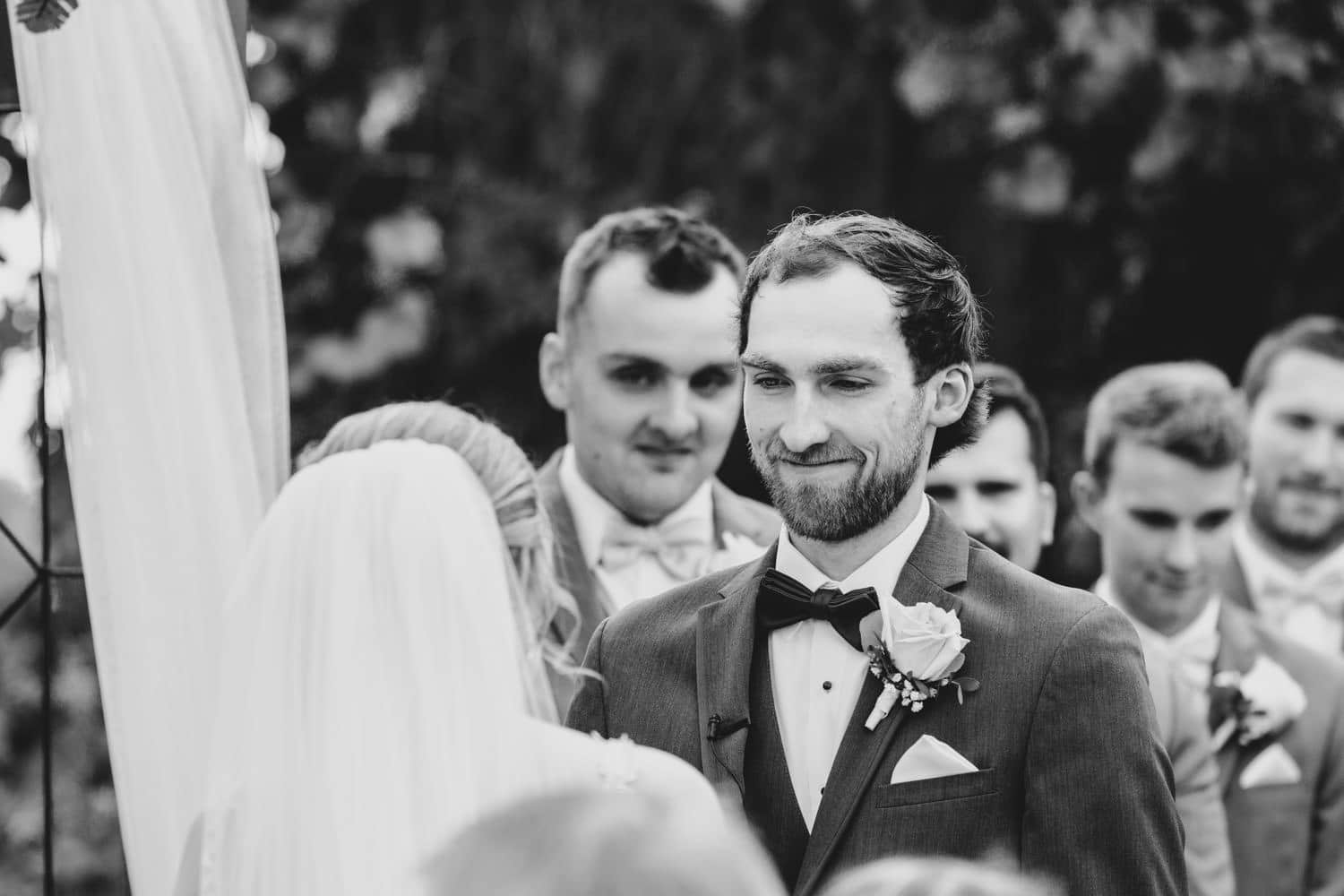 groom listens to vows - outdoor summer wedding