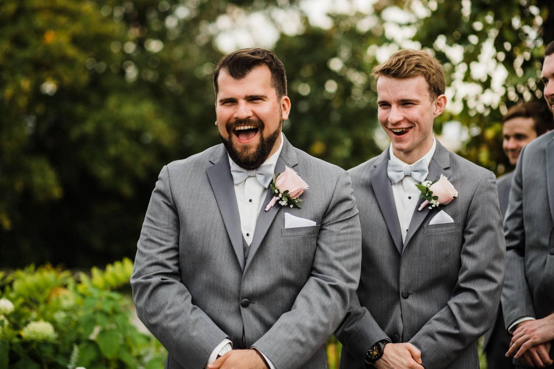 groomsmen laugh during ceremony - outdoor summer wedding