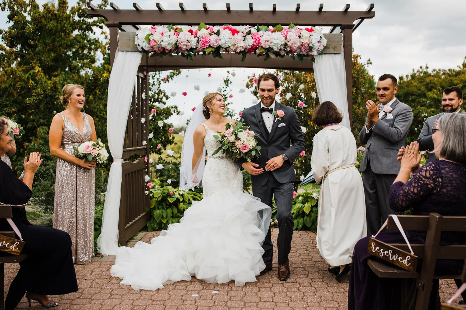 bride and groom laugh while walking down aisle together - summer strathmere wedding