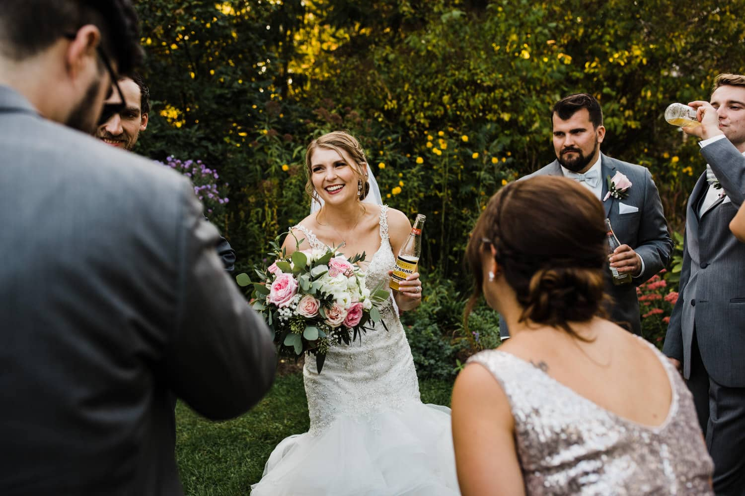 bride laughs with wedding party while having a drink in the garden - strathmere summer wedding