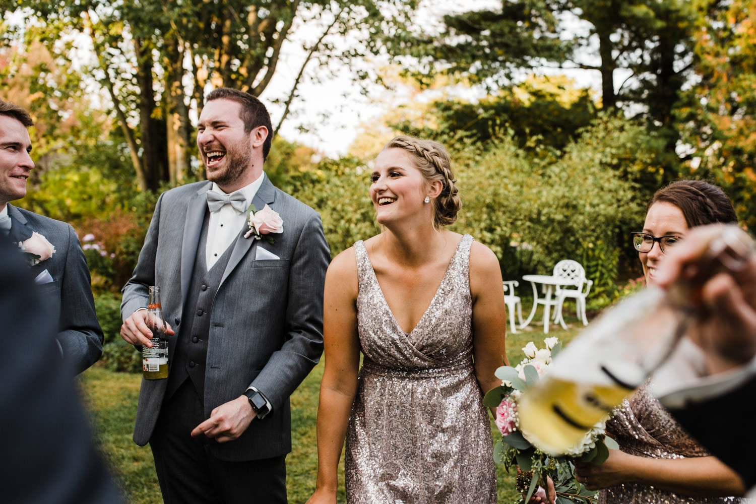 wedding party laughs together in the garden - strathmere summer wedding