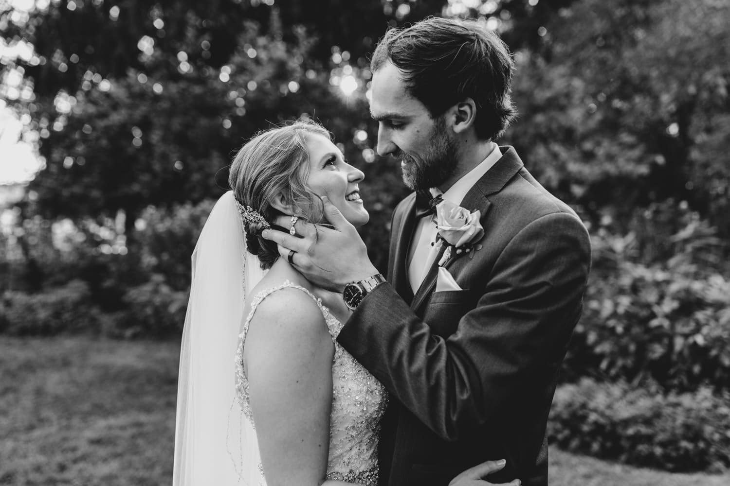 groom holds his brides face close