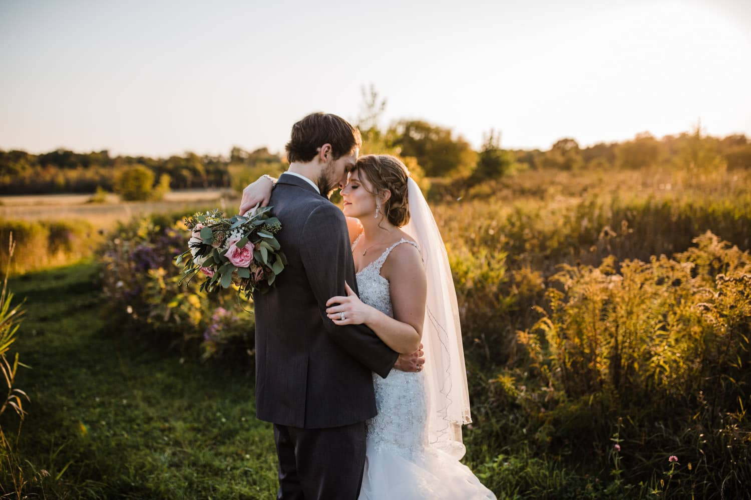 bride and groom stand quietly together outside at sunset
