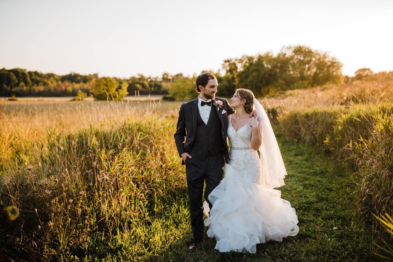 bride and groom walk down outdoor pathway together - strathmere summer wedding