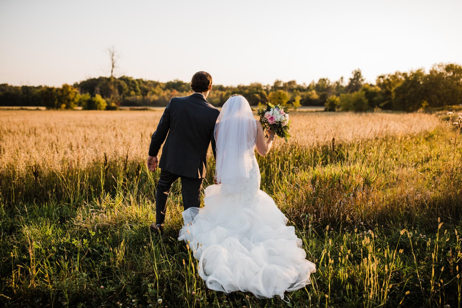 bride and groom walk through field during golden hour