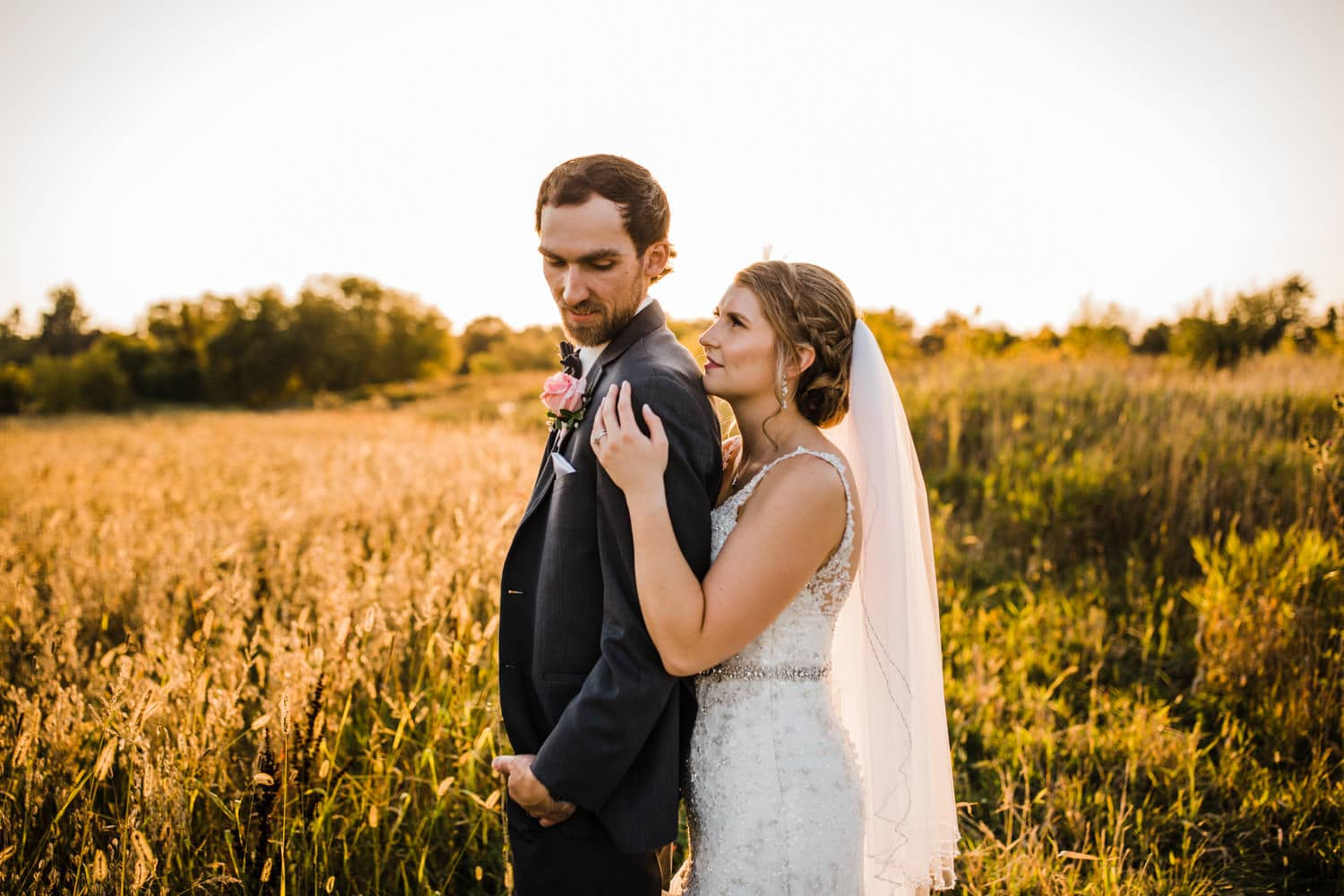 bride and groom stand in field during golden hour - strathmere summer wedding