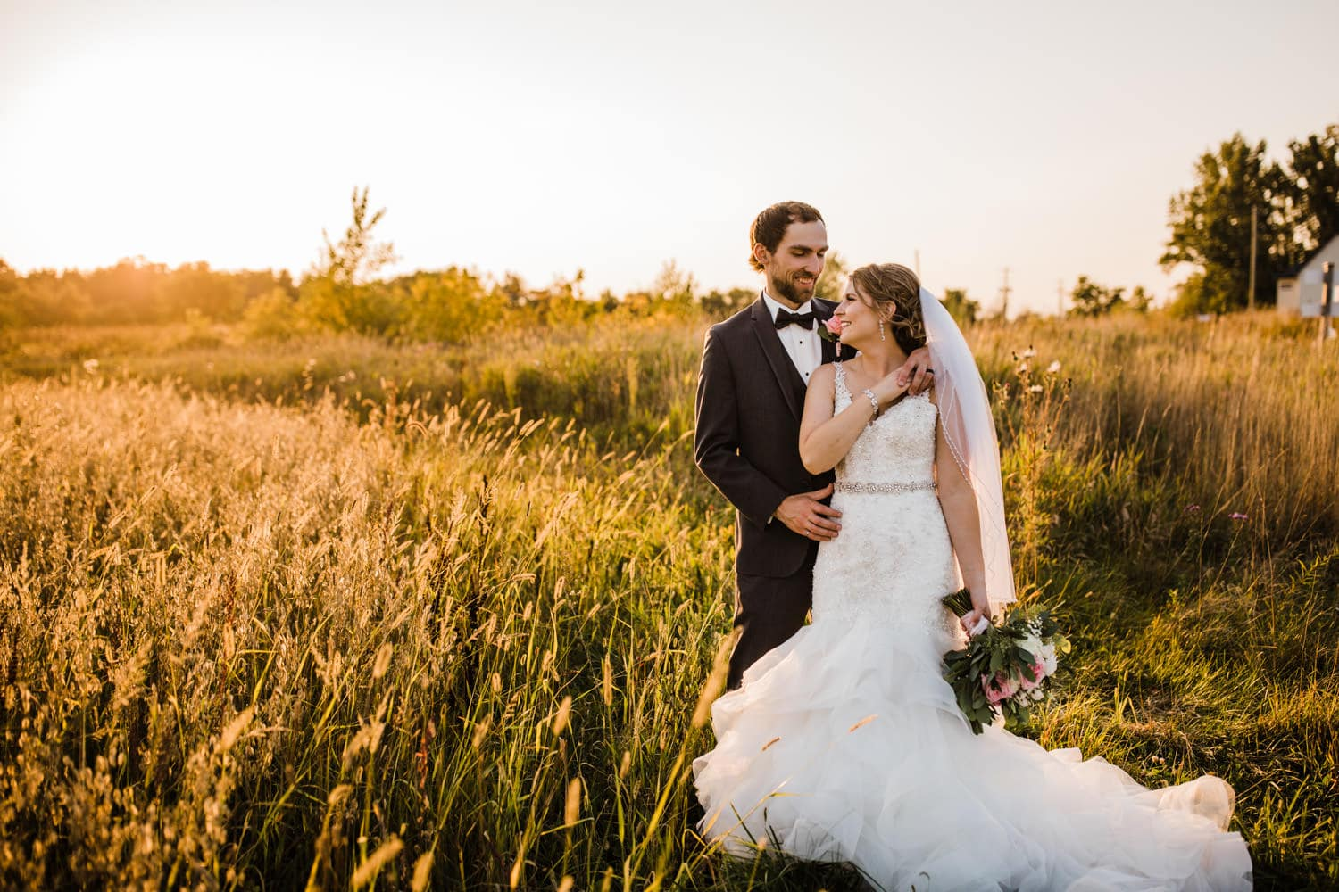 bride and groom laugh together in a field during golden hour