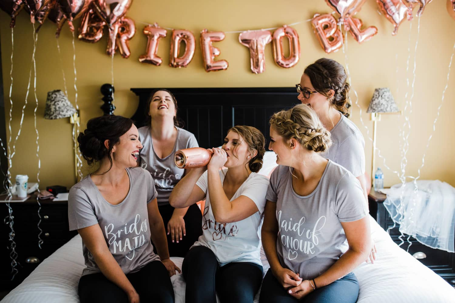 bride chugs champagne and laughs with her bridesmaids