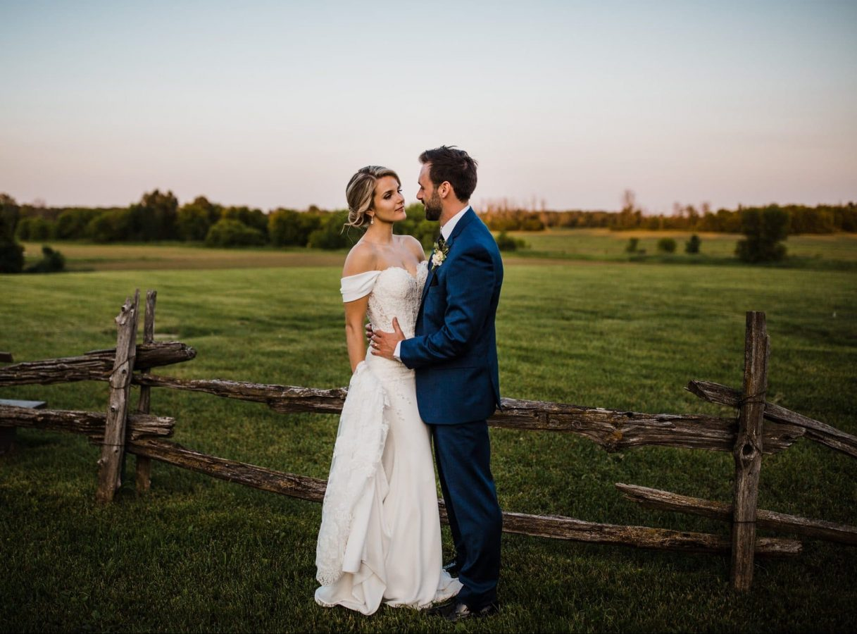 bride and groom stand close by wood fence at sunset - ottawa wedding photographer
