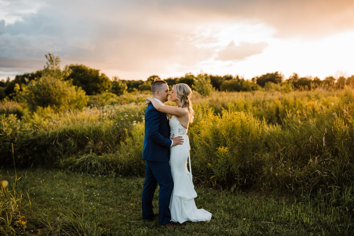 bride and groom snuggle outside together at sunset - ottawa wedding photographer