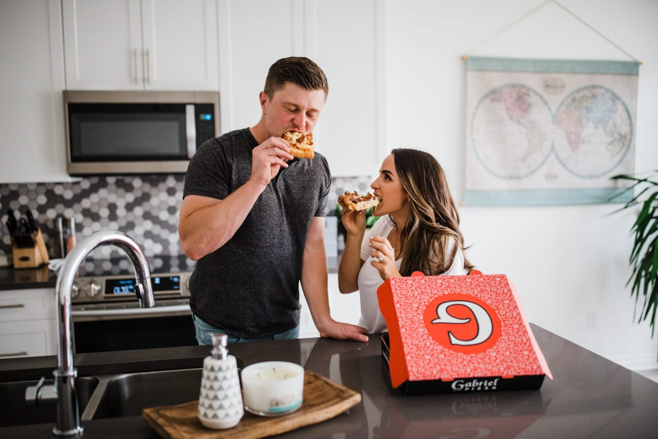 couple eat pizza on the counter in their kitchen - ottawa engagement photographer - at home engagement