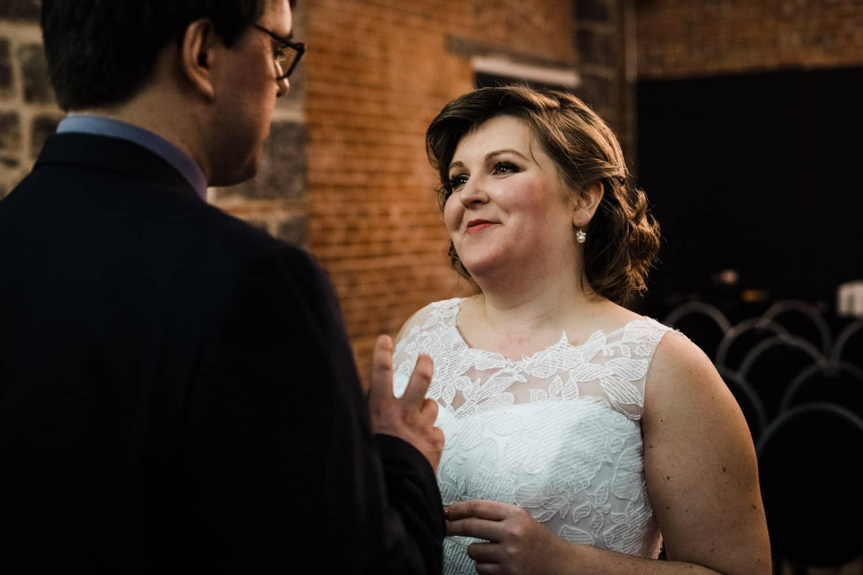 bride looks at groom in chapel