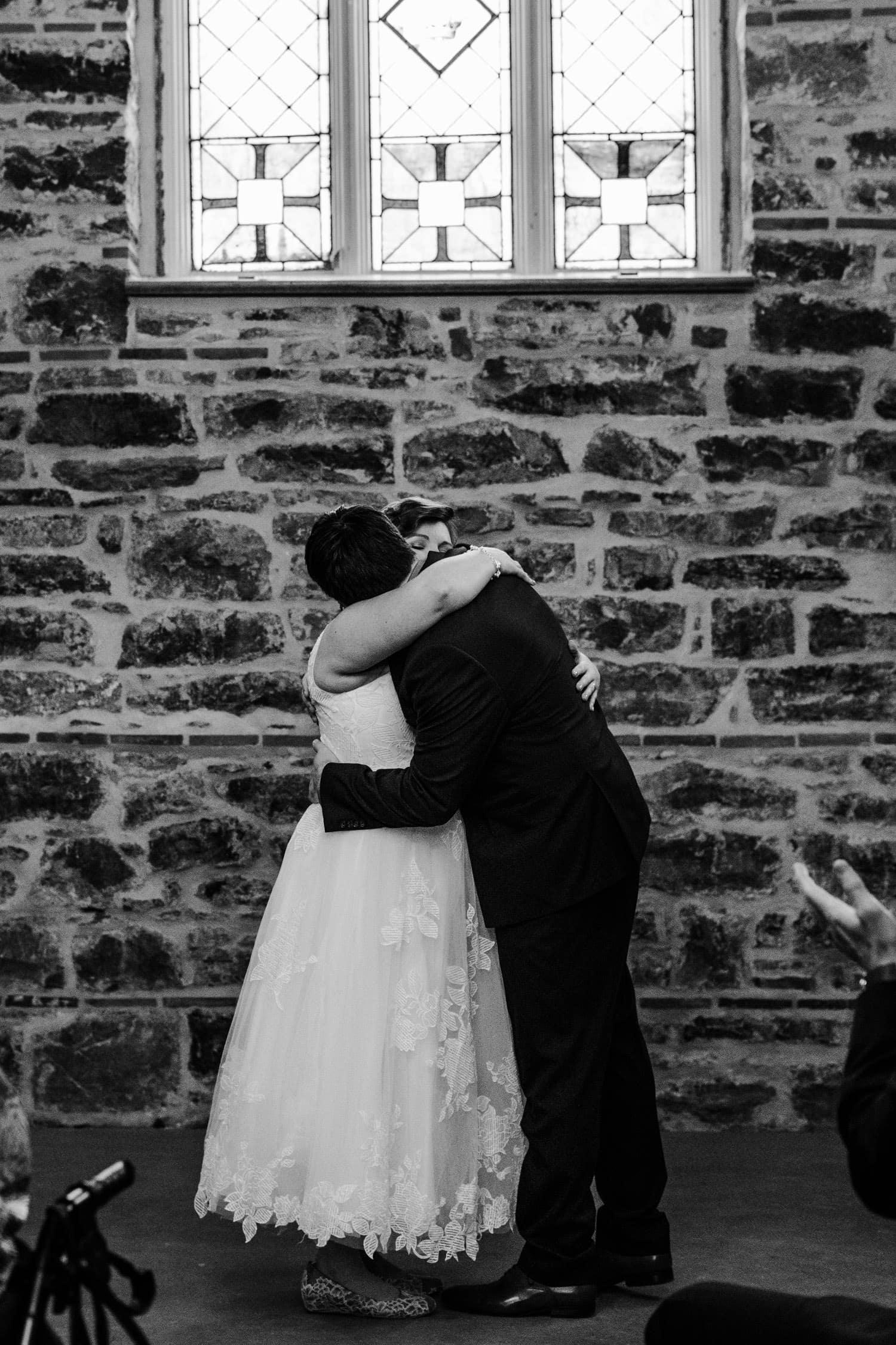 bride and groom hug after intimate winter wedding ceremony