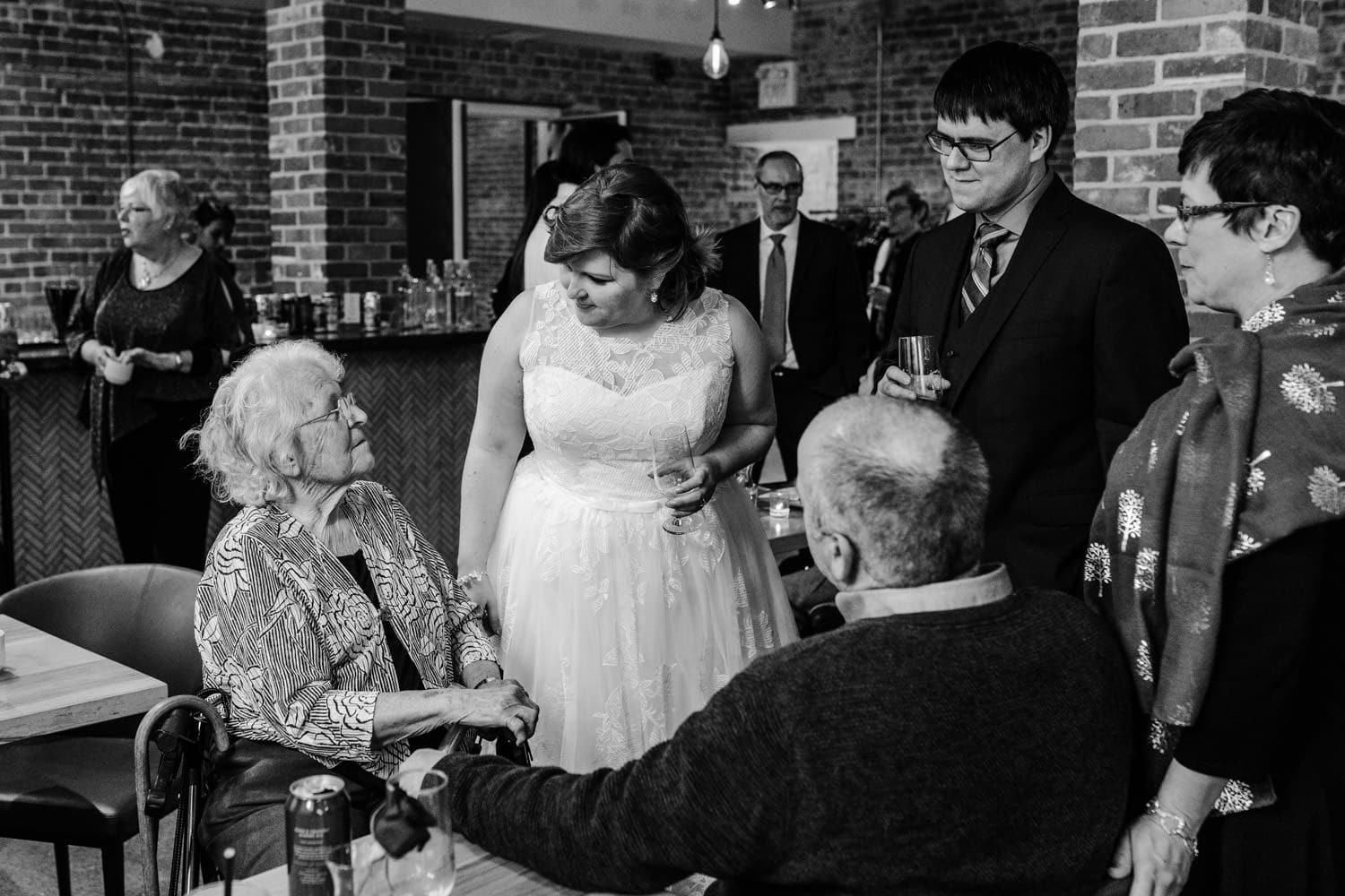 bride and groom talk with grandmother after wedding ceremony